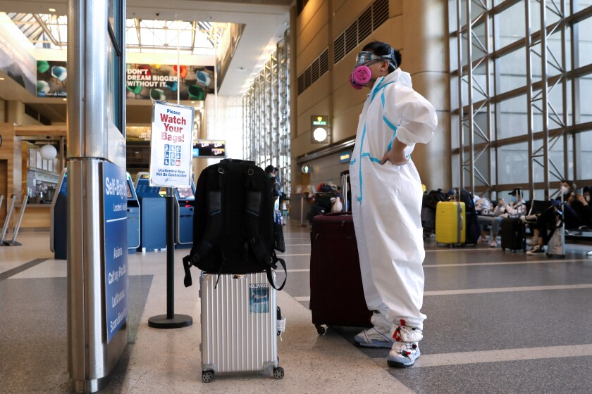 A passenger wearing personal protective equipment checks his flight status in the Tom Bradley International Terminal at Los Angeles International Airport on Wednesday.