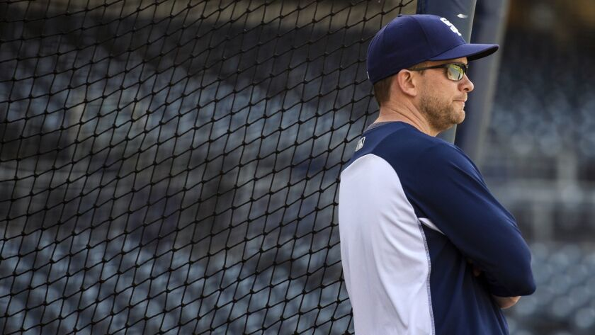 San Diego Padres manager Andy Green watches his players warm up before a baseball game against the N