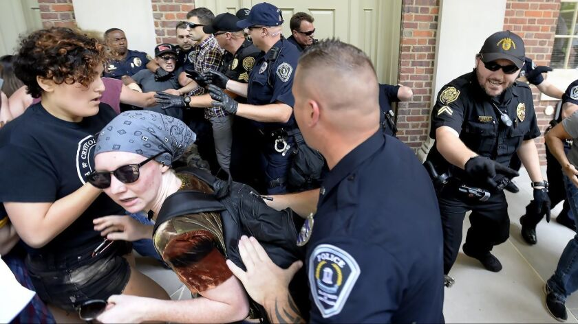 Protesters scuffle with police during a rally in front of Graham Memorial Building on the campus of