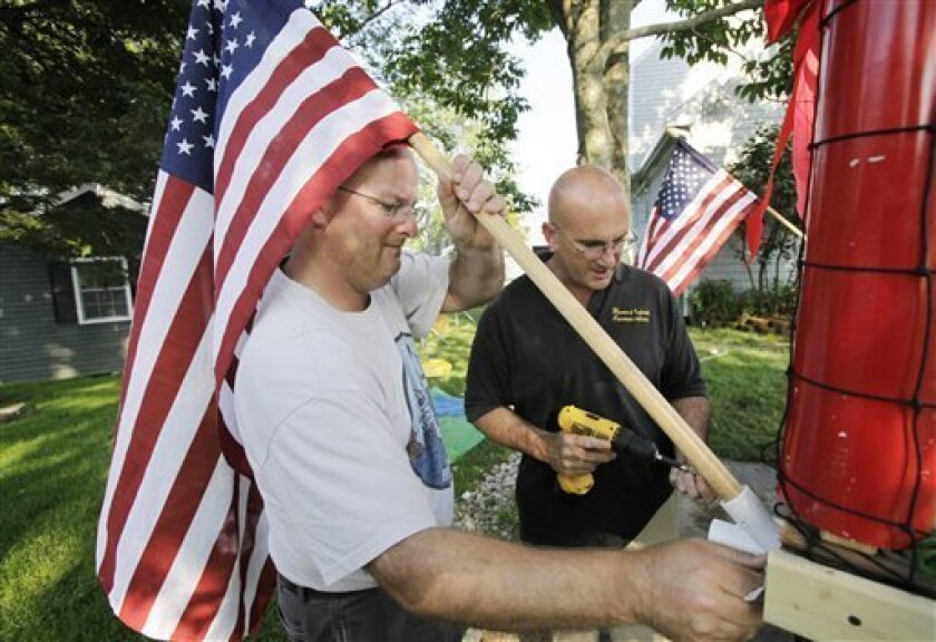 Kris Larson, left, and Peter Lopes attach an American flag to a soccer-themed Independence Day parade float in Bristol, R.I., Monday, June 30, 2009. Bristol residents have marked July 4th every year since 1785, allowing the town to lay claim to the nation's oldest Independence Day celebration. (AP Photo/Steven Senne)