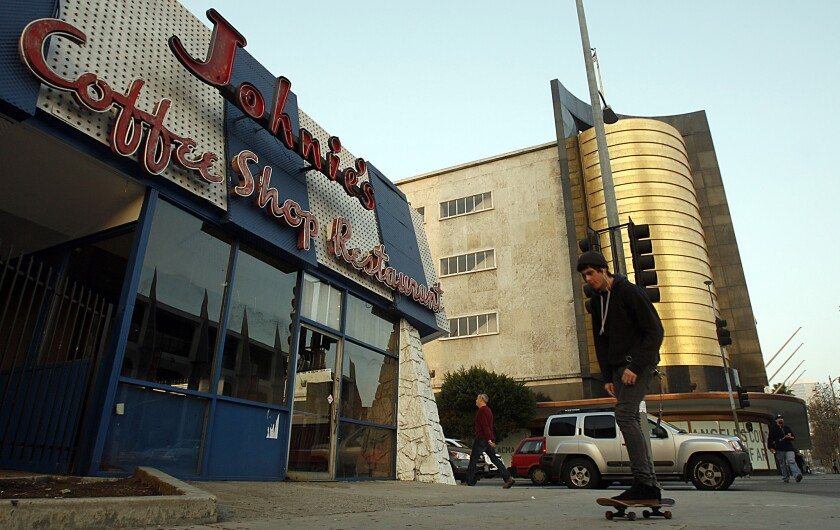 A skateboarder passes Johnie's Coffee Shop and the former May Co. department store on Wilshire Boulevard.