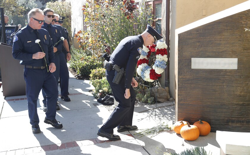 A Laguna Beach police officer places a flower on the fallen officers memorial wall.