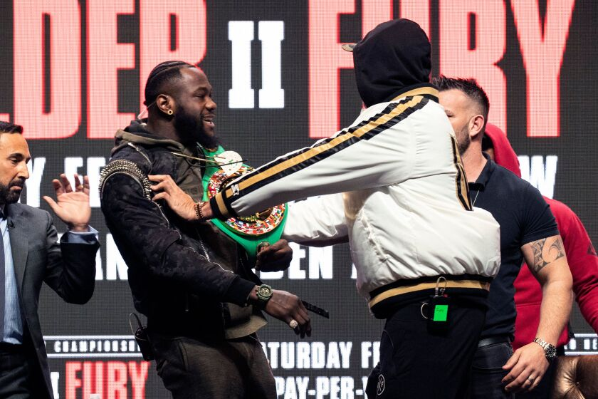 Deontay Wilder, left, and Tyson Fury II push each other on stage prior to their last press conference in Las Vegas on Wednesday.