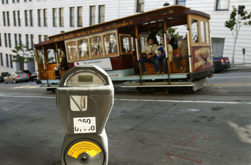 FILE - In this Oct. 27, 2009 file photo, a cable car passes a parking meter near San Francisco's financial district. San Francisco City Attorney Dennis Herrera on Monday, June 23, 2014 issued a cease-and-desist demand to a mobile app called Monkey Parking, which allows people to auction off public