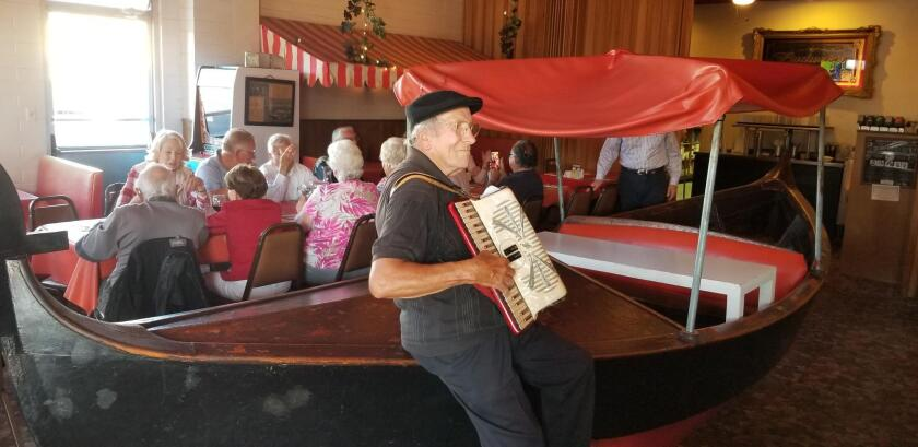John Pernicano leans against the legendary boat in his restaurant while entertaining Thursday night diners and Kiwanis Club members.