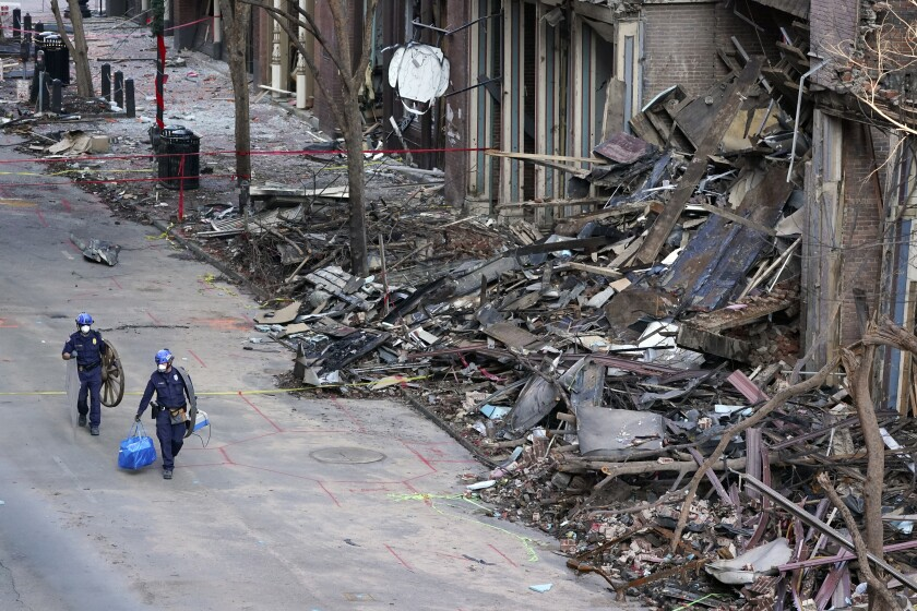 FILE - In this Jan. 4, 2021, file photo, police officers walk past damaged buildings in Nashville, Tenn. The FBI investigation into whether the Nashville bombing was a terrorist act has sparked criticism about a possible racial double standard and drawn questions from downtown business owners whose insurance coverage could be affected by the bureau's assessment. (AP Photo/Mark Humphrey, File)