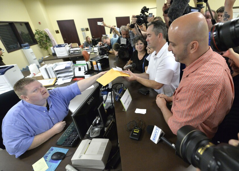 Deputy Rowan County Clerk Brian Mason, left, hands James Yates and William Smith Jr. their marriage license at the Rowan County Judicial Center in Morehead, Ky., on Sept. 4.