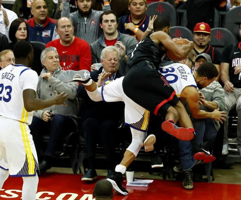 El jugador Stephen Curry (d) de Golden State Warriors en acción ante Trevor Ariza (c) de Houston Rockets durante un partido de la NBA entre Golden State Warriors y Houston Rockets. EFE