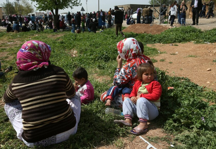 In this picture taken on Monday, April 20, 2015, Kurdish refugees who fled from Kobani wait for the opening of a border gate to return to their town, at the Mursitpinar border crossing in Suruc town, Turkey. Three months since Kobani was liberated, tens of thousands of its residents are still stran