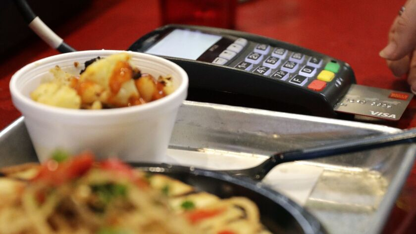 A customer uses a credit card to pay for a meal at Peli Peli Kitchen in Houston.