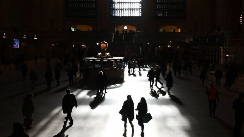 Commuters walk through the morning sunlight coming through the windows in New York's Grand Central Terminal on March 11, the first workday morning after daylight saving time took effect.