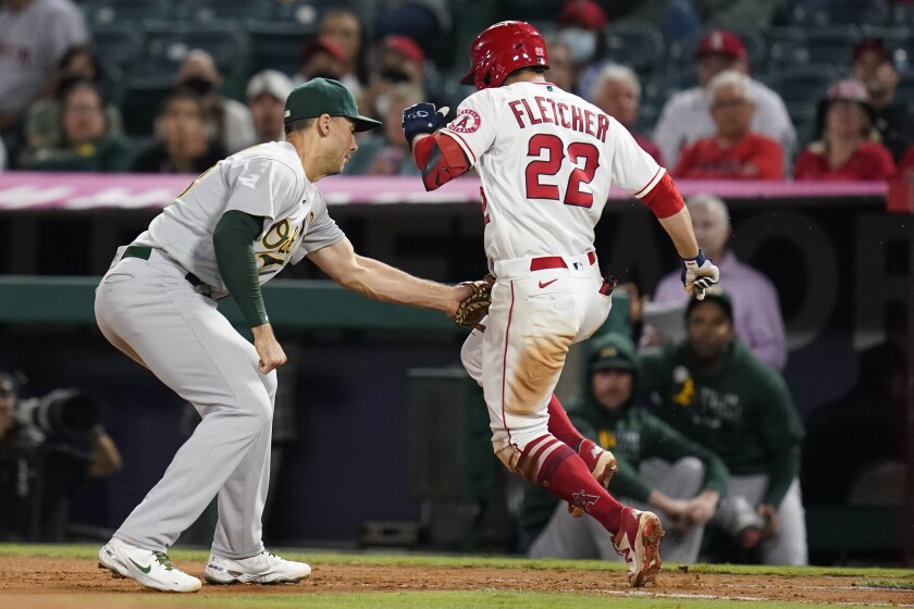 David Fletcher (22), de los Angelinos de Los Ángeles, es eliminado por el primera base de los Atléticos de Oakland Matt Olson en el séptimo inning del juego de la MLB que enfrentó a ambos equipos el 17 de septiembre de 2021, en Anaheim, California. (AP Foto/Ashley Landis)