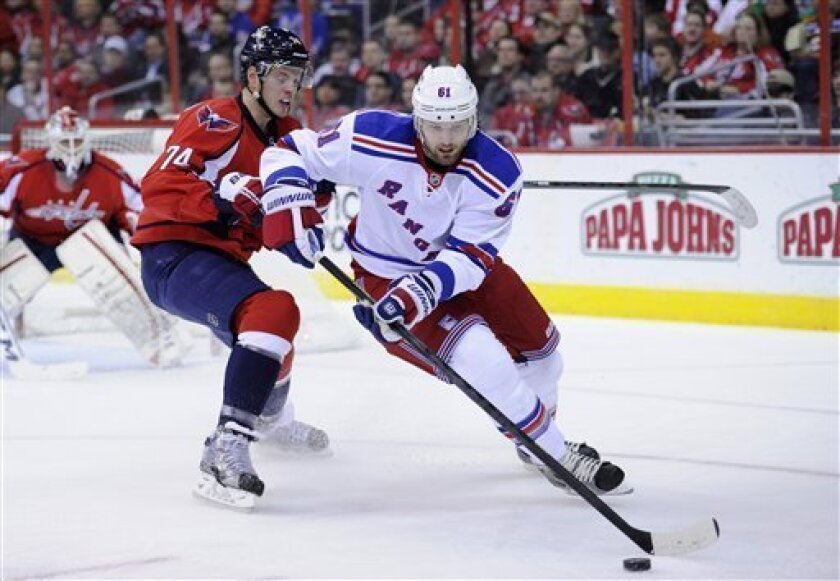 New York Rangers left wing Rick Nash (61) works the puck against Washington Capitals defenseman John Carlson (74) during the second period of an NHL hockey game, Sunday, March 10, 2013, in Washington. (AP Photo/Nick Wass)
