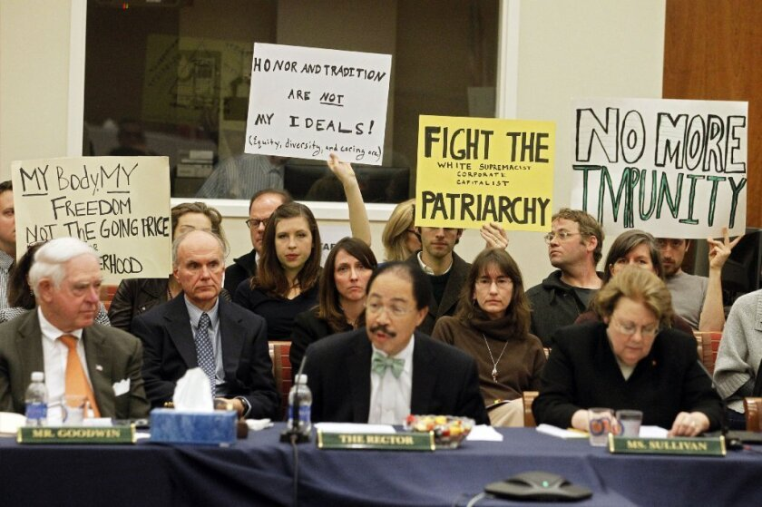 Members of the audience hold signs during a board of visitors meeting about sexual assault at the University of Virginia last week.