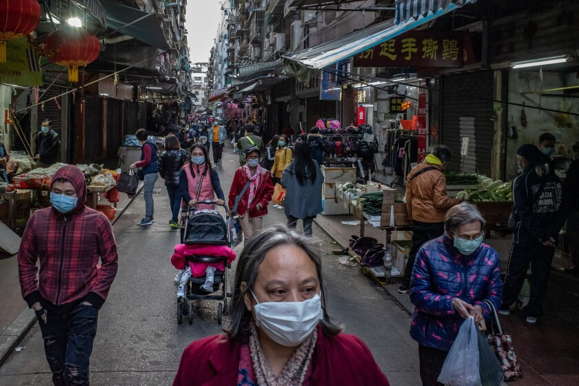 Shoppers wear face masks to guard against spreading the coronavirus at a market this week in Macau, China.