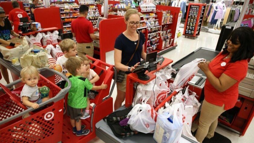 Merideth Lembke, of Brookfield, and her four children check out with the help of cashier Gina Spurlin at the Super Target store in Broadview on July 20, 2018. The retailer reported March 5, 2019, that its store traffic was up 4.5 percent chainwide.