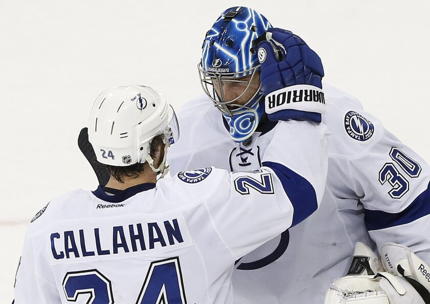 Tampa Bay Lightning goalie Ben Bishop (30) is congratulated by right wing Ryan Callahan (24) after shutting out the New York Rangers 2-0 in Game 5 of the Eastern Conference final during the NHL hockey Stanley Cup playoffs, Sunday, May 24, 2015, in New York. (AP Photo/Kathy Willens)