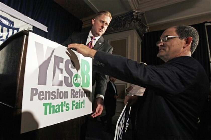 FILE - Supporters of Proposition B, which would roll back public pensions, adjust a sign before a rally on election day in San Diego in this Tuesday, June 5, 2012 file photo. For years, companies have been chipping away at workers' pensions. Now, two California cities may help pave the way for gove