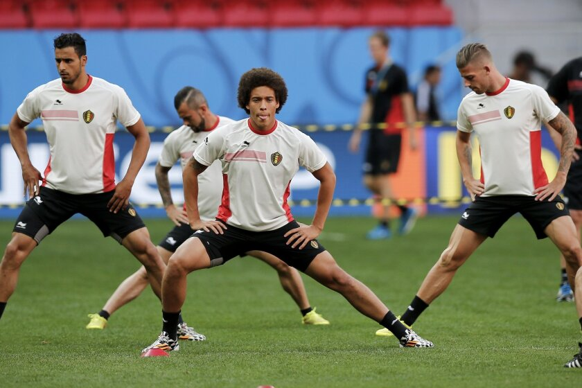 Belgium's Axel Witsel, center, stretches next to teammates during a practice session at Estadio Nacional in Brasilia, Brazil, Friday, July 4, 2014. On Saturday, Belgium will face Argentina in their World Cup quarterfinals soccer match. (AP Photo/Victor R. Caivano)