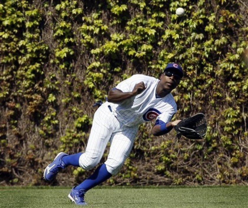 Chicago Cubs left fielder Alfonso Soriano dives to catch a fly ball from Washington Nationals' Adam LaRoche during the fourth inning of a baseball game in Chicago, Sunday, April 8, 2012. (AP Photo/Nam Y. Huh)