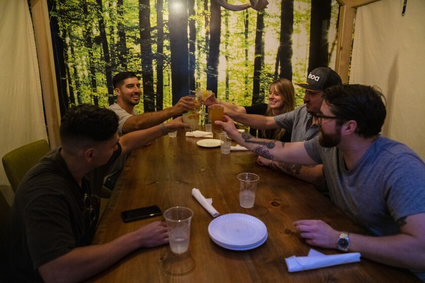 Friends begin with a toast before dinner underneath a cabana at One Door North restaurant in North Park on Friday. This was their groups first dinner outing together since the coronavirus pandemic.
