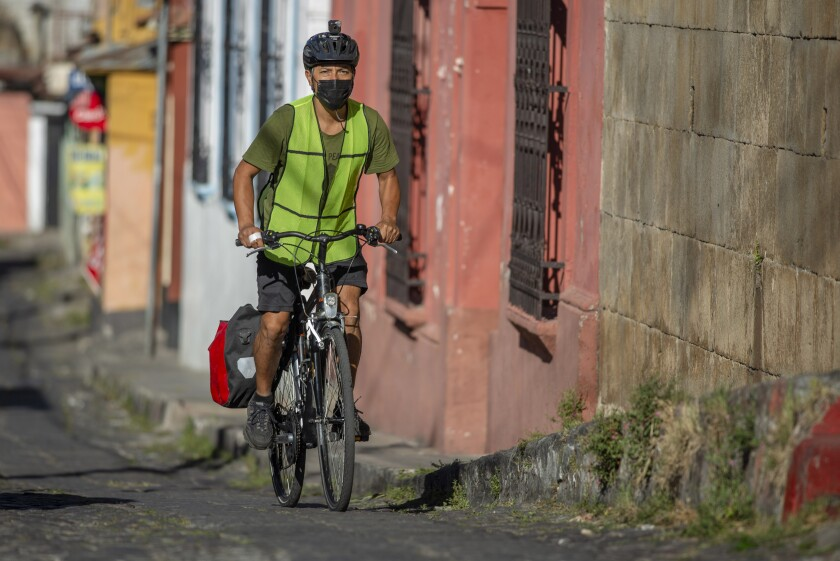 Bonifaz Diaz rides through the streets of Quetzaltenango, Guatemala, Saturday, Jan. 30, 2021. Diaz has pedaled thousands of miles to carry books that people can barter for bags of a cereal mix aimed at providing relief to families suffering chronic malnutrition. (Henning Sac via AP)