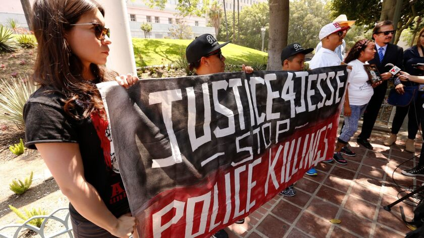 At a news conference last year, Sol Marquez, left, with Centro Community Service Organization, holds a sign in support of 14-year-old Jesse Romero, who was fatally shot by Los Angeles police in 2016.