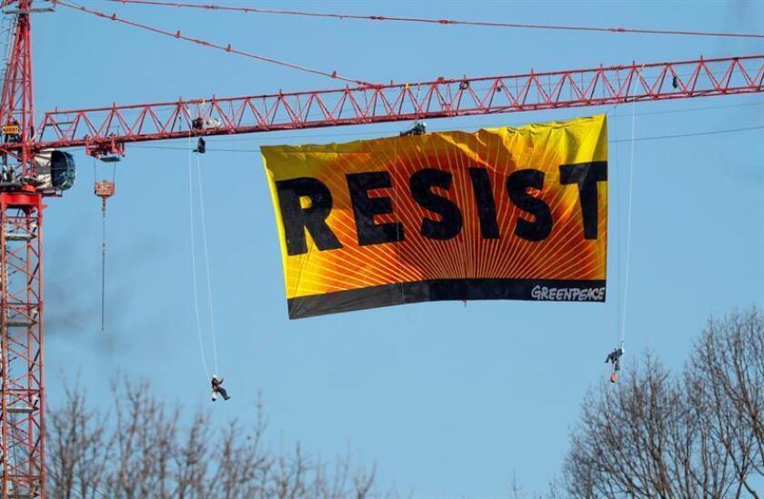 """La organización medioambiental Greenpeace desplegó hoy en una grúa cerca de la Casa Blanca un gran cartel que llama a """"Resistir"""", un día después de que el presidente, Donald Trump, diera luz verde a la construcción de dos oleoductos. EFE"""