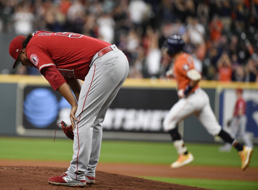 Angels pitcher Jaime Barria reacts after giving up a two-run homer to the Astros' Carlos Correa, background, on Sept. 20, 2019.