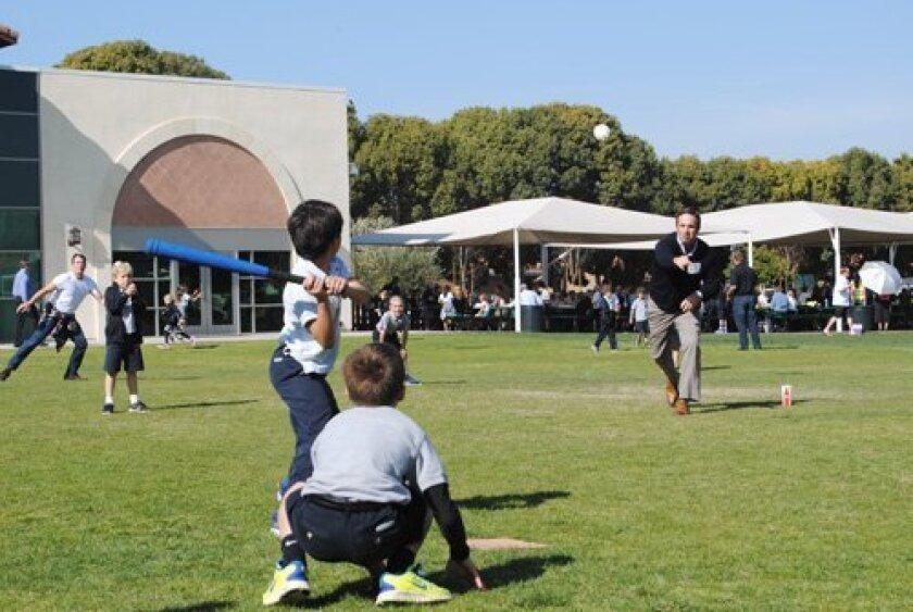 Horizon Prep second grader Elijah Segoria takes a swing at Brian Guiltinan's fast whiffle ball at Dad's Day.