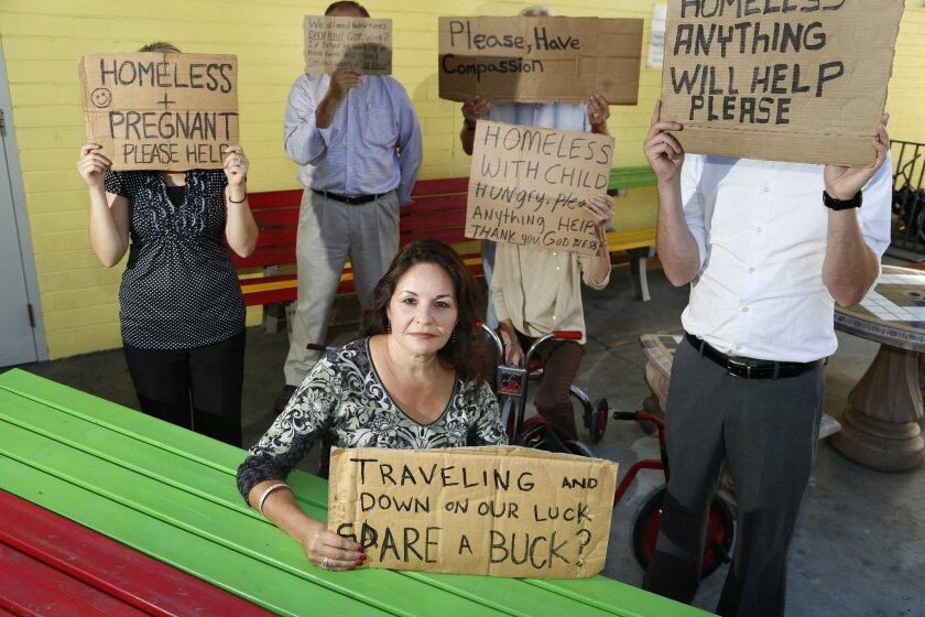San Diego Rescue Mission volunteer Linda Lopez is surrounded by cardboard signs made by homeless people and collected by her for an exhibit to be displayed a the upcoming Sleepless in San Diego Event.