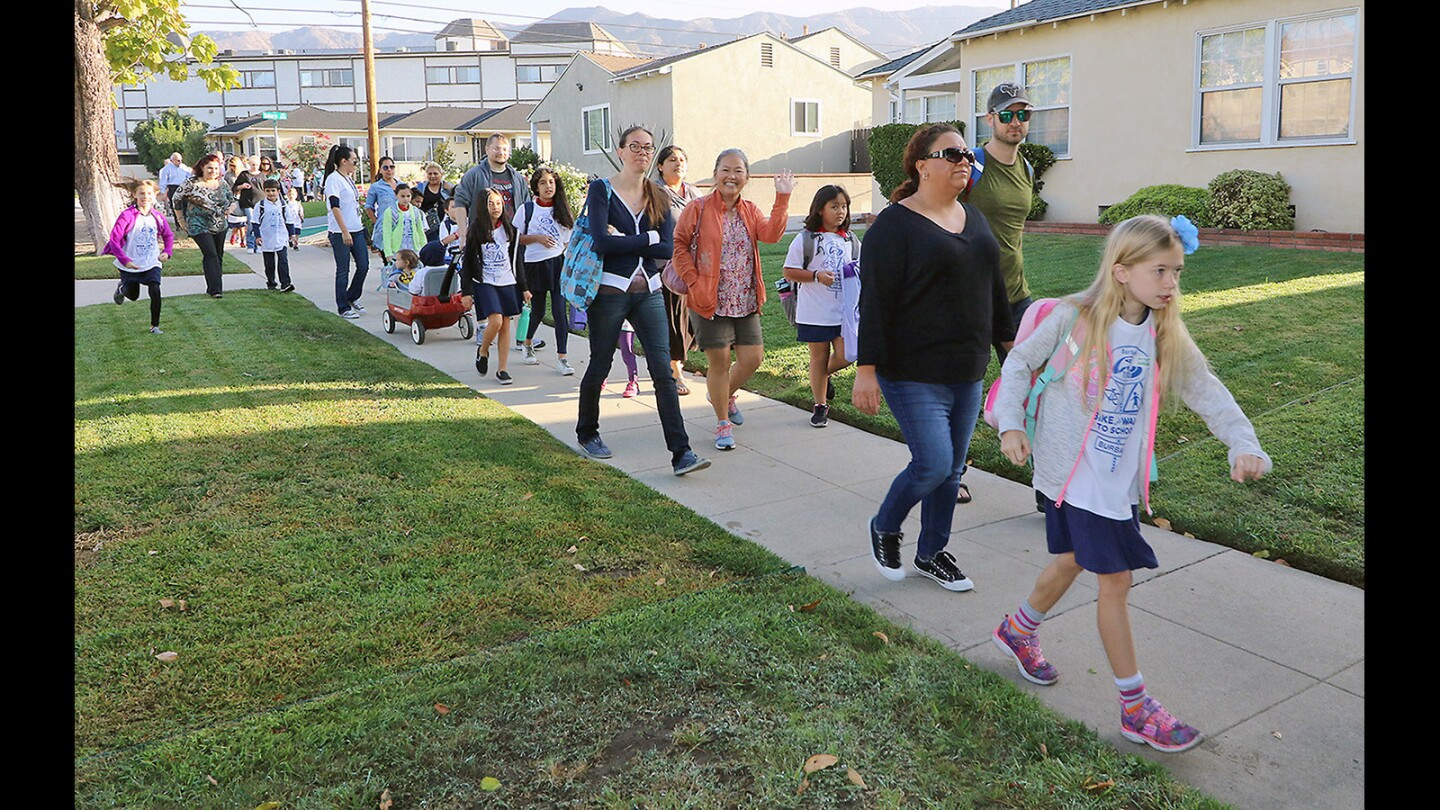 Family members walk along one of the designated safe routes to Washington Elementary on Wednesday, October 4, 2017.
