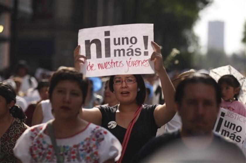 """People march during a protest against violence in Mexico City, Wednesday, April 6, 2011. The continuing tide of drug-related killings in Mexico has drawn thousands of protesters into the streets of Mexico's capital and several other cities, in marches against violence. The sign reads in Spanish """"Not one more of our young men!"""" (AP Photo/Alexandre Meneghini)"""