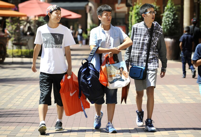 Chinese tourists shop at the Citadel Outlets in Commerce on Aug. 12, 2015. Outbound travel from China grew by 53% last year, according to a new study.
