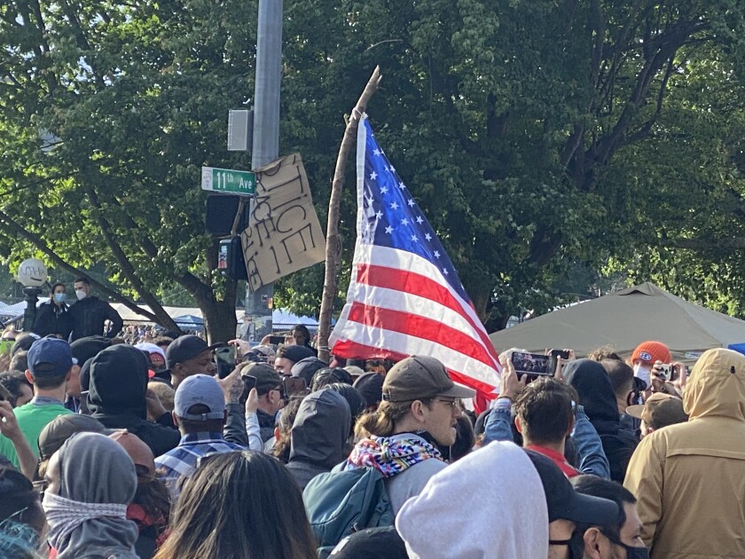 """Activists in Seattle's """"cop free"""" zone converge Saturday on an American flag held by a counter-protester."""