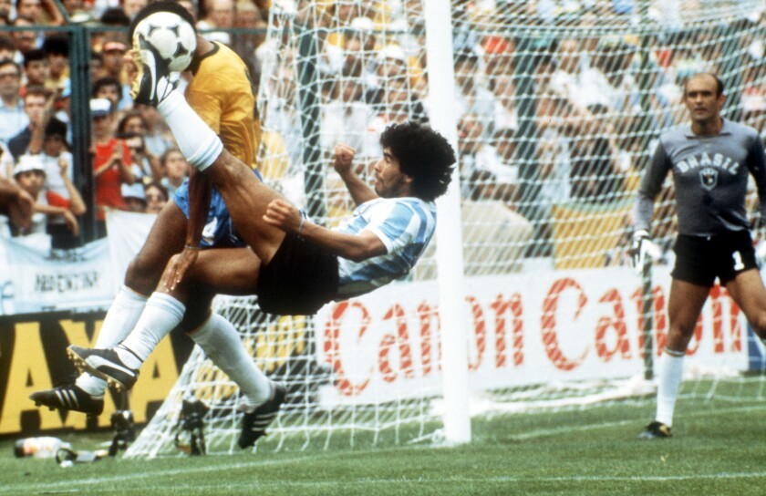 Diego Maradona delivers an overhead kick against Brazilian defender Luizinho in the 1982 FIFA World Cup