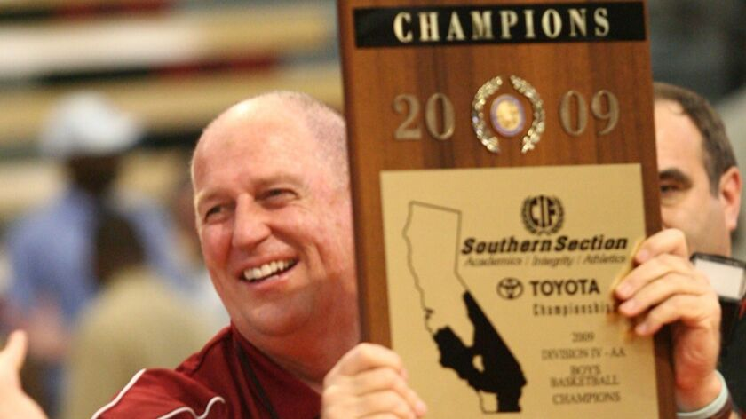 Ocean View basketball coach Jim Harris holds up the championship plaque after his team defeated Ingl