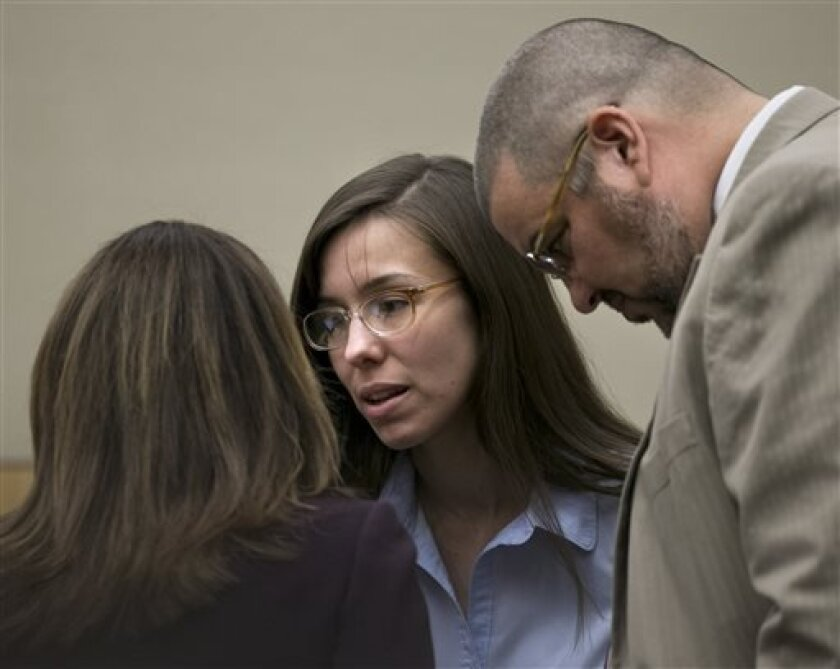 Jodi Arias talks to defense attorneys Jennifer Wilmott and Kirk Nurmi during the Jodi Arias trial at Maricopa County Superior Court in Phoenix on Wednesday, April 3, 2013. Arias is charged with murder in the death of lover Travis Alexander. (AP Photo/The Arizona Republic, David Wallace)