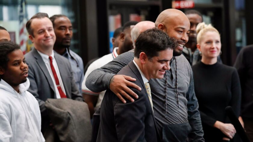 Joshua Tepfer, with the Exoneration Project, is hugged by Leonard Gipson at a news conference Thursday at the Leighton Criminal Court Building in Chicago. Gipson was one of 15 men whose convictions were overturned.