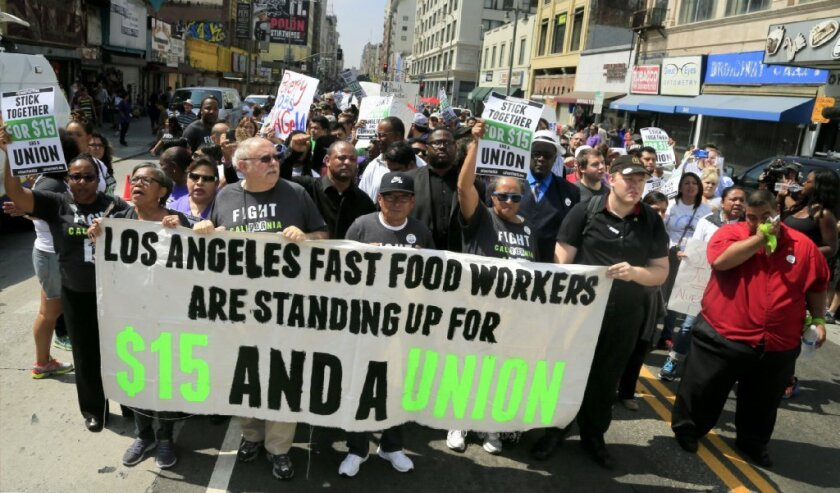 Fast-food workers are joined with other community supporters after marching up Broadway in downtown L.A. during a peaceful demonstration demanding higher wages on Sept. 4.