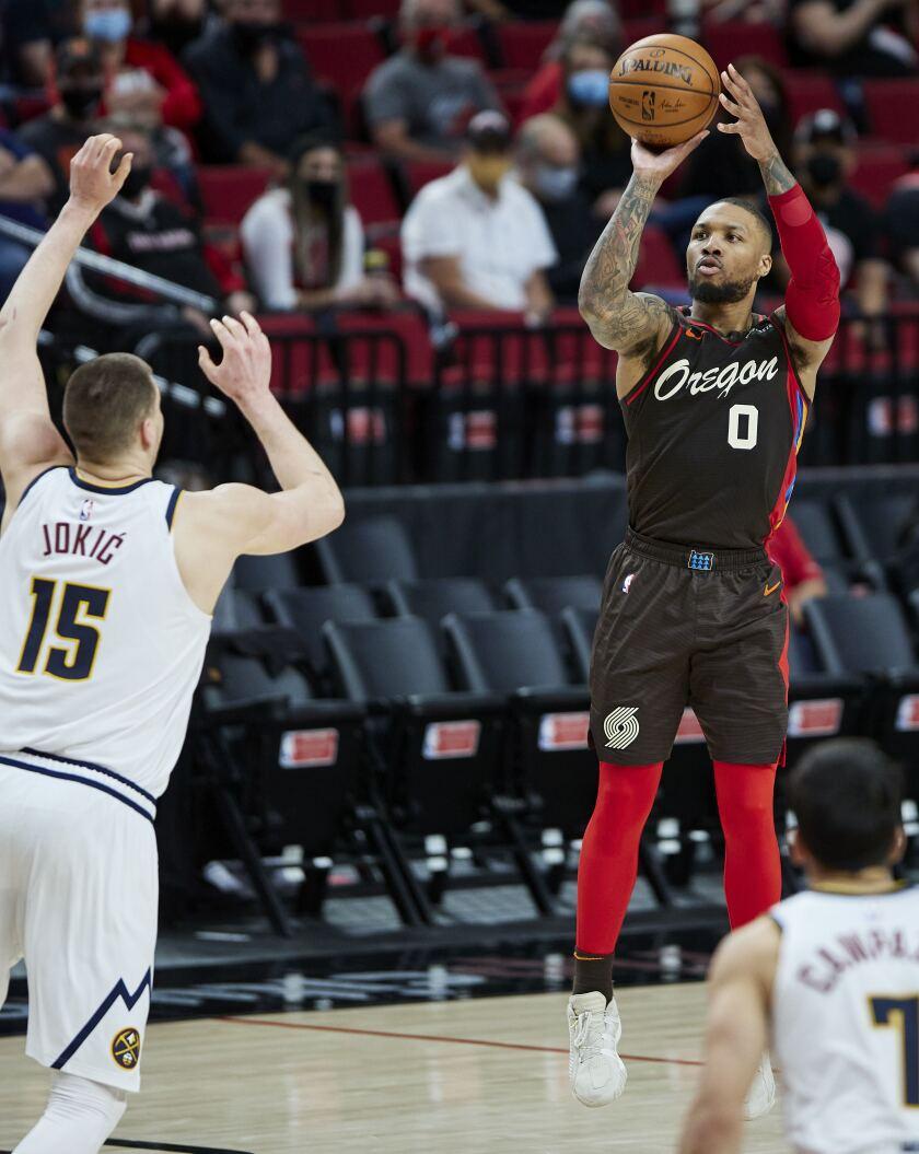 Portland Trail Blazers guard Damian Lillard shoots a 3-pointer Denver Nuggets center Nikola Jokic during the second half of Game 6 of an NBA basketball first-round playoff series Thursday, June 3, 2021, in Portland, Ore. (AP Photo/Craig Mitchelldyer)