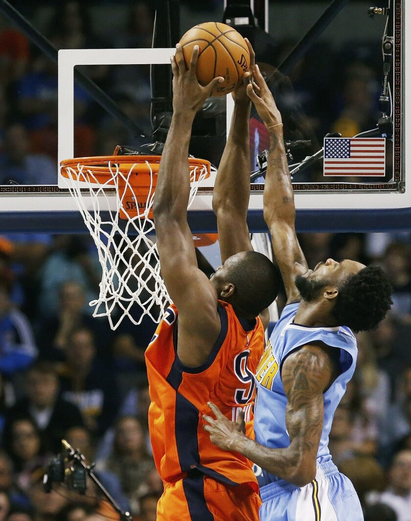 Oklahoma City Thunder forward Serge Ibaka (9) goes up for a dunk in front of Denver Nuggets guard Will Barton, right, in the first half of an NBA basketball game in Oklahoma City, Sunday, Nov. 1, 2015. (AP Photo/Sue Ogrocki)