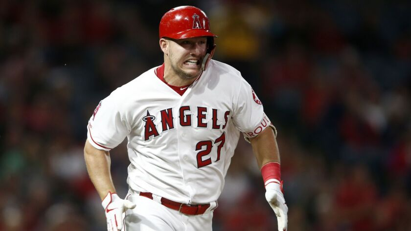 Angels center fielder Mike Trout runs to first after hitting a single against the Milwaukee Brewers on Tuesday.
