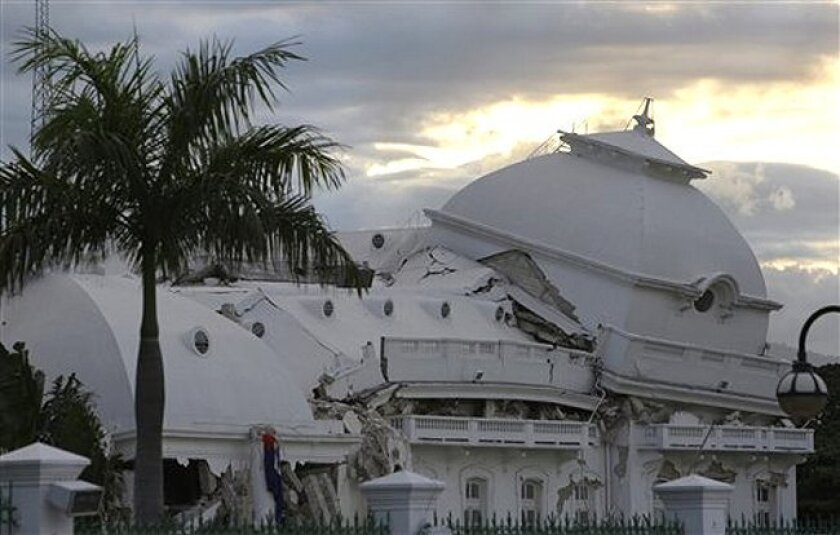 The sun sets behind the crumpled National Palace in Port-au-Prince, Wednesday, Jan. 13, the day after the island's devastating magnitude-7 quake.