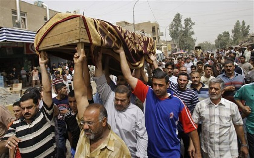 Men carry the coffin of eleven year old Mohammed Akeel who was killed the day before, when a bomb exploded in the Kasra market in northern Baghdad, Iraq, Friday, July 10, 2009. (AP Photo/Khalid Mohammed)