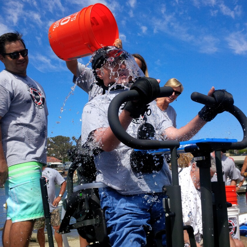 Augie Nieto, center, a Corona del Mar resident who has been living with ALS for the past nine and a half years, completed the ice-bucket challenge Sunday on Balboa Island with his son, Austin, at his side.