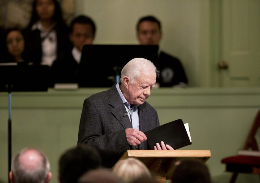 FILE - In this Aug. 23, 2015 file photo, former President Jimmy Carter opens up a Bible while teaching Sunday School class at Maranatha Baptist Church in his hometown in Plains, Ga.  Carter's recent diagnosis that cancer has spread to his brain will require him to scale back his work, but Carter Ce