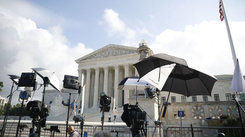 Television camera crews wait outside the Supreme Court in Washington, Tuesday, Oct. 9, 2018.
