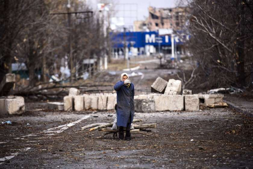 A woman collects firewood in the bombed outskirts of eastern Ukraine's Donetsk airport area. Separatists who won elections to lead the breakaway regions promised to restore peace and order after seven months of war.