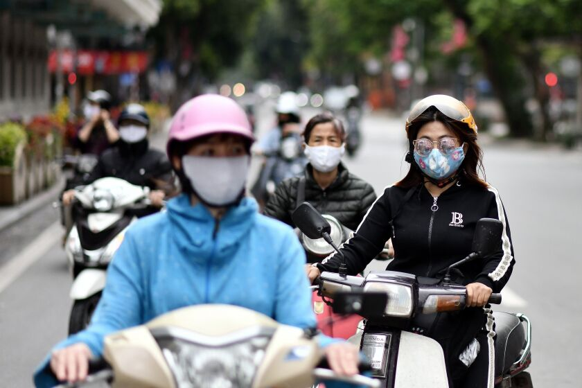Motorists in masks wait at a stoplight in Hanoi, Vietnam